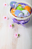 Ovos da páscoa em uma cesta e em flores Imagem de Stock Royalty Free