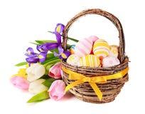 Ovos da páscoa em uma cesta e em flores da mola Imagens de Stock