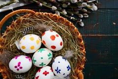 Ovos da páscoa em uma cesta e em ramos do salgueiro Fotos de Stock
