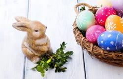 Ovos da páscoa em uma cesta e em um coelho Imagens de Stock Royalty Free