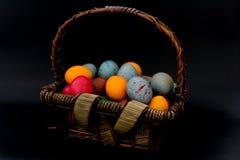 Ovos da páscoa em uma cesta em um foco seletivo do fundo preto Imagem de Stock