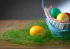 Ovos da páscoa em uma cesta em uma tabela de madeira. Foto de Stock Royalty Free