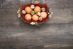 Ovos da páscoa em uma cesta no fundo de madeira Fotografia de Stock Royalty Free