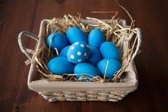 Ovos da páscoa em uma cesta no fundo de madeira rústico, imagem do foco seletivo, Páscoa feliz Imagens de Stock Royalty Free