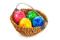 Ovos da páscoa em uma cesta redonda em um fundo branco Imagem de Stock Royalty Free