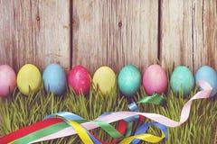 Ovos da páscoa em uma grama verde em um fundo de madeira, decorações autênticas da Páscoa Easter feliz Fotografia de Stock