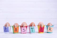 Ovos da páscoa em umas cubetas coloridas Fotografia de Stock Royalty Free