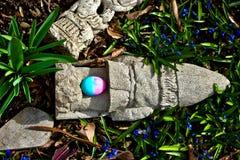 Ovos da páscoa escondidos entre a decoração caída do jardim situada entre a florescência das flores imagens de stock royalty free