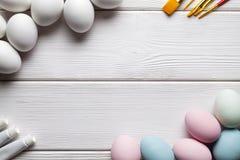 Ovos da páscoa, escovas e pinturas brancos e coloridos na tabela branca Fotos de Stock Royalty Free