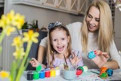 Ovos da páscoa felizes da pintura da mãe e da filha na sala de visitas Imagens de Stock Royalty Free
