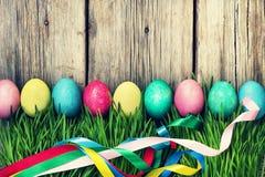 Ovos da páscoa FELIZES em uma grama verde em um fundo de madeira, decorações autênticas da PÁSCOA da Páscoa Imagem de Stock Royalty Free