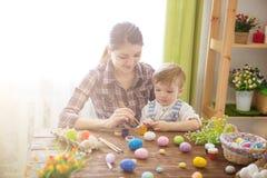 Ovos da páscoa felizes da pintura da mamã da família e do filho das crianças com cores Preparação para o feriado imagem de stock royalty free