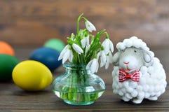 Ovos da páscoa, flores da mola e estatueta bonito dos carneiros Fotografia de Stock Royalty Free