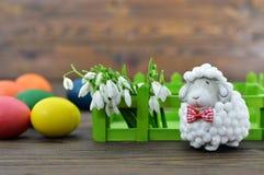 Ovos da páscoa, flores da mola e estatueta bonito dos carneiros Imagens de Stock