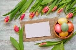 Ovos da páscoa na bacia e nas tulipas com um cartão branco no fundo de madeira do vintage foto de stock royalty free