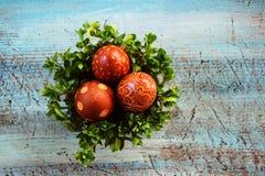 Ovos da páscoa na bacia na mesa azul fotografia de stock