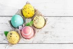 Ovos da páscoa na caixa dos desenhos animados do ovo no fundo de madeira rústico branco Imagens de Stock Royalty Free