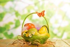 Ovos da páscoa na cesta, na borboleta e na fita no verde abstrato Foto de Stock