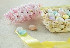 Ovos da páscoa na cesta com fita amarela e o botão fresco do jacinto cor-de-rosa Imagem de Stock