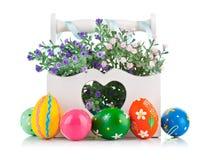 Ovos da páscoa na cesta de madeira com flores da mola Imagem de Stock