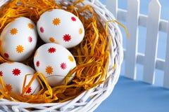Ovos da páscoa na cesta e na cerca branca Imagem de Stock