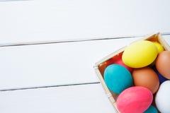 Ovos da páscoa na cesta na tabela de madeira Easter feliz Foto de Stock