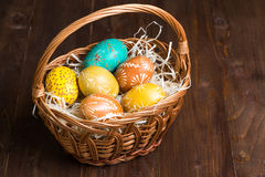 Ovos da páscoa na cesta no fundo da madeira da cor Fotografia de Stock