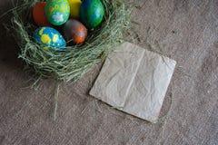 Ovos da páscoa no feno com papel de embalagem Imagens de Stock Royalty Free