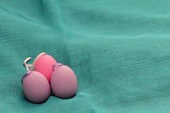 Ovos da páscoa no fundo ciano Ovos da páscoa decorativos roxos na textura azul do fundo Ovo roxo com a bacia em ciano Imagem de Stock