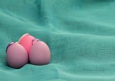Ovos da páscoa no fundo ciano Ovos da páscoa decorativos roxos na textura azul do fundo Ovo roxo com a bacia em ciano Fotografia de Stock