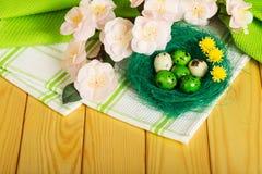 Ovos da páscoa no ninho, flores na toalha e árvore da luz imagens de stock