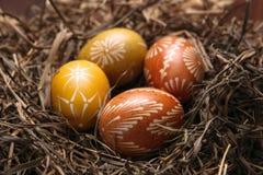 Ovos da páscoa no ninho no fundo de madeira da cor Imagem de Stock Royalty Free