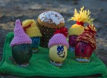 Ovos da páscoa nos tampões, com as caras engraçadas na natureza Fotografia de Stock Royalty Free