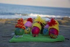 Ovos da páscoa nos tampões, com as caras engraçadas na natureza Imagens de Stock