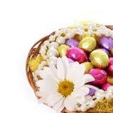 Ovos da páscoa, ovos de chocolate coloridos com flor da camomila e colares da pérola na cesta fotografia de stock