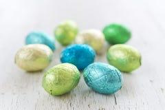 Ovos da páscoa pequenos do chocolate em um fundo branco rústico Foto de Stock Royalty Free