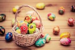 Ovos da páscoa pintados à mão coloridos na cesta e na madeira Decoração feito a mão do vintage foto de stock