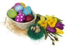Ovos da páscoa pintados à mão no ninho do ` s do pássaro e na cesta Imagem de Stock