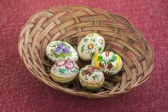 Ovos da páscoa pintados coloridos na cesta de vime marrom, vida tradicional da Páscoa ainda, flores pintadas Fotos de Stock Royalty Free