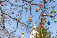 Ovos da páscoa pintados em um ramo de árvore A igreja no fundo fotografia de stock