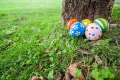 Ovos da páscoa pintados escondidos na grama atrás de um tronco de árvore Imagem de Stock