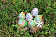 Ovos da páscoa pintados escondidos na grama, pronta para o jogo tradicional do jogo da caça do ovo da páscoa Imagem de Stock