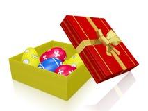 Ovos da páscoa pintados na caixa de presente com a fita da curva do ouro Fotos de Stock