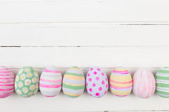 Ovos da páscoa pintados nas cores pastel em uma madeira branca Fotos de Stock