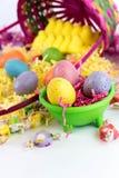 Ovos da páscoa, pintainhos, doces e cesta coloridos Fotos de Stock