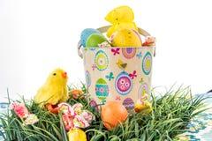 Ovos da páscoa, pintainhos, doces e cubeta coloridos na grama Foto de Stock Royalty Free