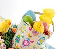 Ovos da páscoa, pintainhos, doces e cubeta coloridos na grama Imagens de Stock Royalty Free