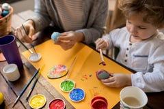 Ovos da páscoa da pintura de Little Boy com mãe imagens de stock royalty free