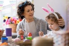 Ovos da páscoa da pintura da mãe e do filho foto de stock royalty free
