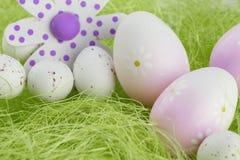 Ovos da páscoa que sentam-se na grama e na flor Imagens de Stock Royalty Free